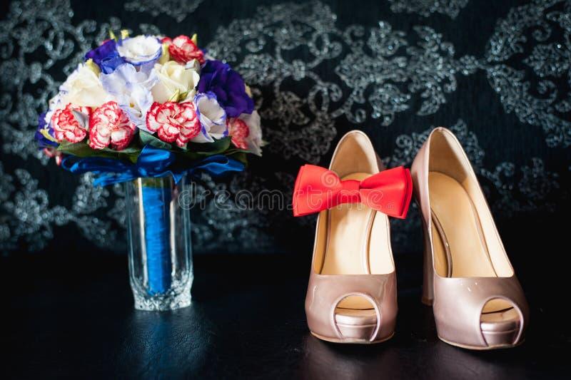 Närbilden av den brud- buketten av rosor som gifta sig blommar för ceremonin på den svarta tabellen i ett hotellrum med vita skor fotografering för bildbyråer