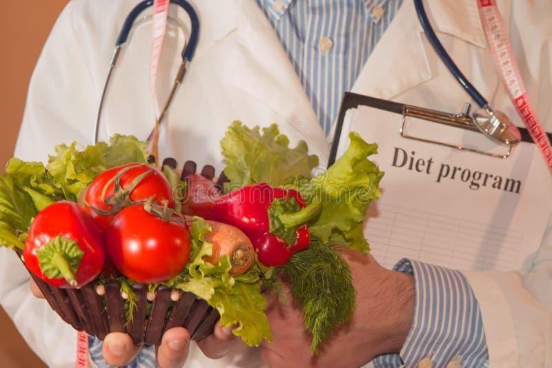 Närbilden av den manliga näringsfysiologen räcker att mäta grönsaker med bandet Stående av den manliga dietisten With Fresh Veget fotografering för bildbyråer