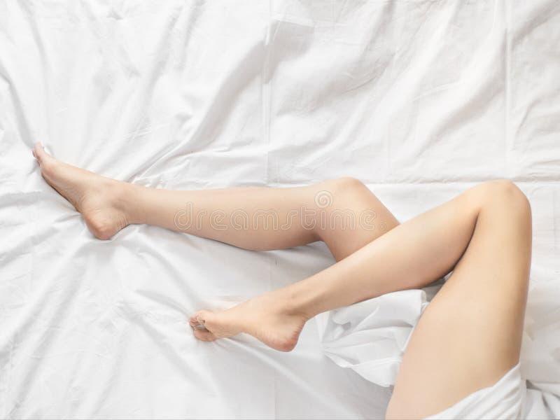 Närbilden av den mjuka kvinnlign lägger benen på ryggen under bedcloth över vit bakgrund royaltyfria foton
