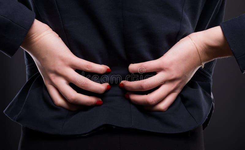 Närbilden av den unga affärskvinnan lider från ryggvärk royaltyfri bild