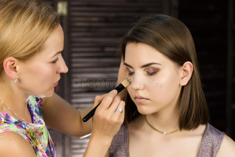 Närbilden av den yrkesmässiga sminkkonstnären som gör daglig makeup, sätter pulver på kvinnans kinder med borsten royaltyfria foton