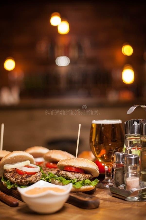 Närbilden av det läckra nya hemmet gjorde hamburgare med grönsallat, ost och tomaten med vit sås på ett cuttinbräde royaltyfria foton