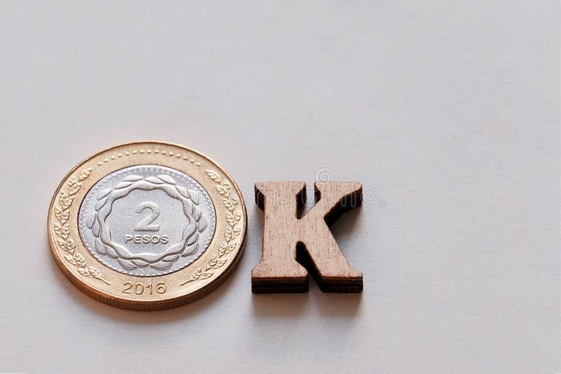 Närbilden av det reko ordet gjorde från 2 pesomynt och träbokstäver på en vit bakgrund Argentina valuta Begreppet av fotografering för bildbyråer
