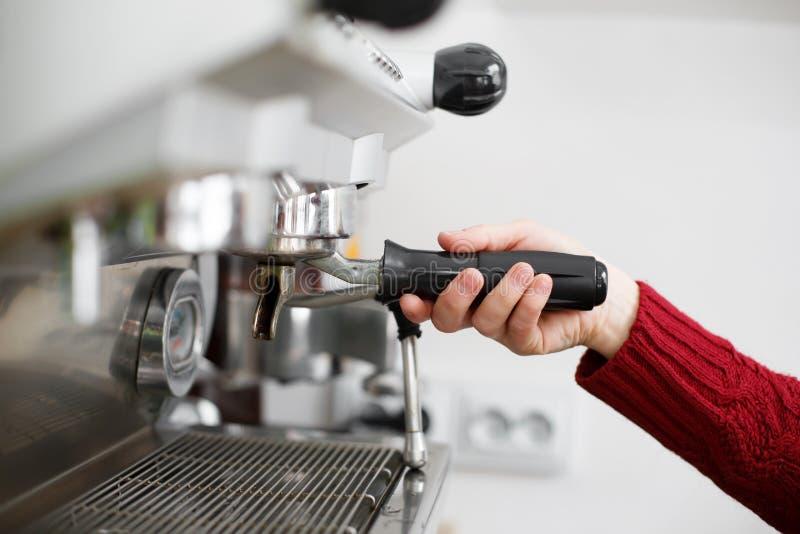 Närbilden av en baristahand installerar en kaffekopp för kaffebryggare royaltyfri foto