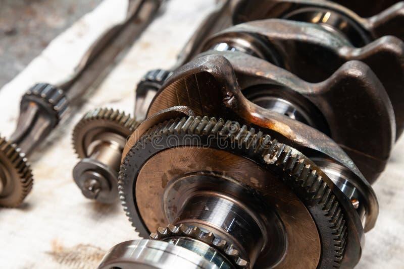 Närbilden av en bilvevaxel och axeln med kugghjul och lager som tas bort för utbytet på en arbetsbänk i en medelreparation, shopp royaltyfria foton