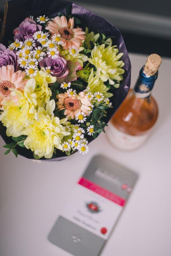 Närbilden av en bukett av färgrika blommor i purpurfärgade förpackande ställningar, steg vin och lyxig choklad på en vit tabell royaltyfri fotografi