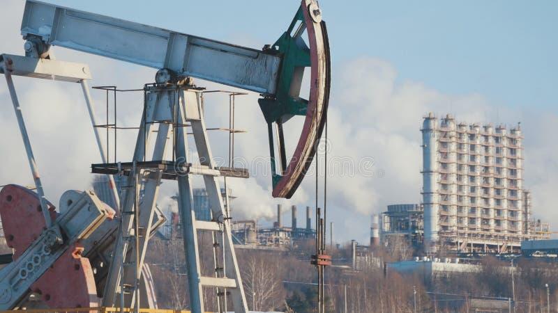 Närbilden av en funktionsduglig pump för extraktionen av råolja och av en ` s för petrokemisk växt leda i rör utsläpp arkivfoton