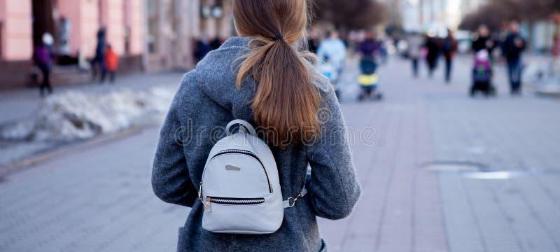 Närbilden av en härlig brunettflicka med långt hår i ett lag går runt om staden i våren, sikt bakifrån royaltyfri foto