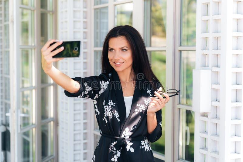 Närbilden av en härlig ung flicka återtog hennes exponeringsglas, har ett europeiskt utseende, mörkt rakt hår, är iklätt a arkivfoto
