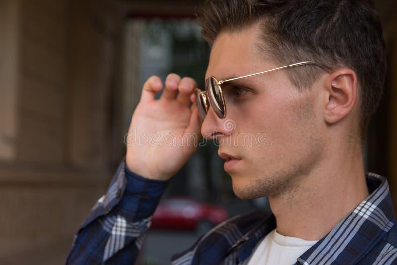 närbilden av en man, som tar av hans solglasögon, den manliga ståenden i profil, var han rymmer exponeringsglas, trycker på expon royaltyfri bild