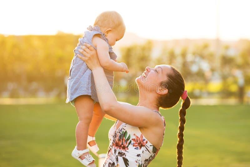 Närbilden av en moder som bär henne, behandla som ett barn dottern royaltyfria foton