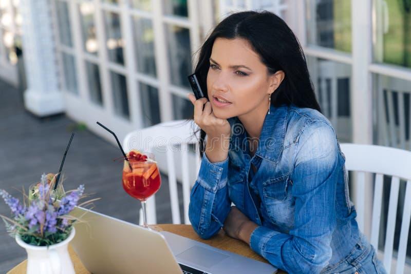 Närbilden av en stilfull ung flicka med ett krås, bruk en bärbar dator, håll en kreditkort i hennes hand, önskar att köpa på någo arkivbilder