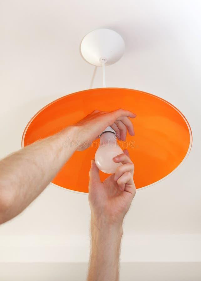 Närbilden av energi-besparingen LEDDE den ljusa kulan i den mänskliga handen, utbytet av lampan i takluminairen royaltyfria foton