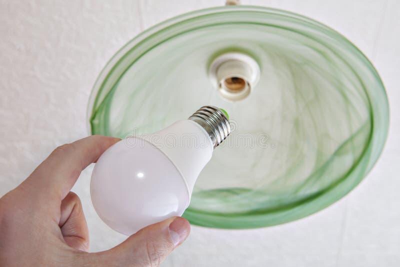 Närbilden av energi-besparingen LEDDE den ljusa kulan i mänsklig hand arkivbilder