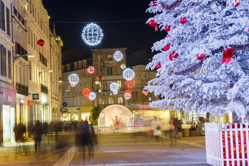 Närbilden av ett snöig träd för jul med den upplysta gatan med shoppar på båda sidan i backgroen royaltyfri foto
