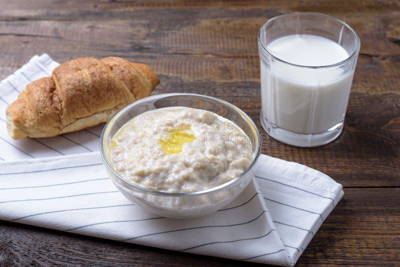 Närbilden av exponeringsglasbunken med havremjölet, exponeringsglas av mjölkar och gifflet, sund frukost arkivfoton