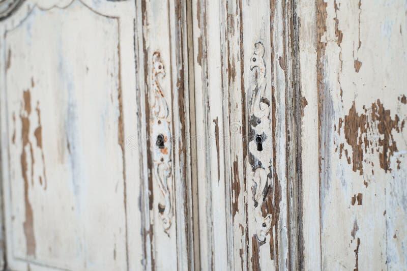 Närbilden av för byråbyrån för nyckelhålet forntida vitt möblemang med målarfärg skalade av royaltyfri bild