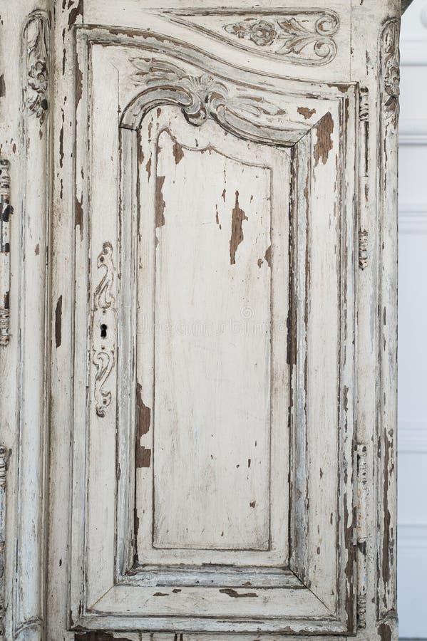 Närbilden av för byråbyrån för nyckelhålet forntida vitt möblemang med målarfärg skalade av royaltyfria bilder