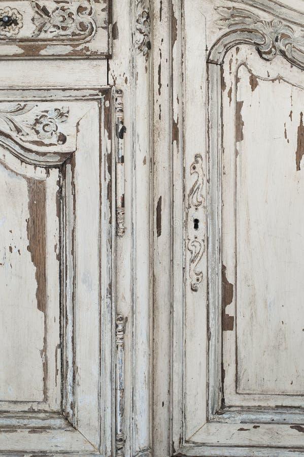 Närbilden av för byråbyrån för nyckelhålet forntida vitt möblemang med målarfärg skalade av arkivfoto