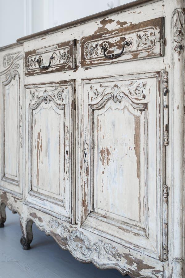 Närbilden av forntida vitt byråbyråmöblemang med målarfärg skalade av arkivfoton