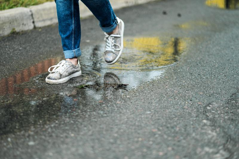Närbilden av fot i gymnastikskor går till och med pölarna på trottoaren arkivbild