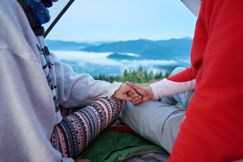 Närbilden av grabb- och flickainnehavet räcker sammanträde i tält på suddiga bakgrundsberg fotografering för bildbyråer