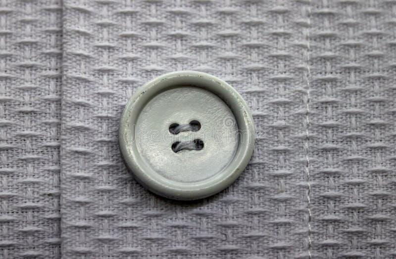 Närbilden av greigeknappen sydde på ljusare kyperttygplagg med att sy arkivbilder