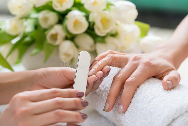 Närbilden av händerna av kvalificerat spara för manikyrist spikar arkivbild