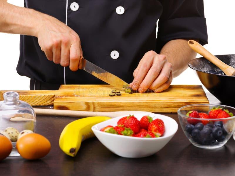 Närbilden av handen för kock` s i förklädet, en stor kniv skivade druvor arkivbild