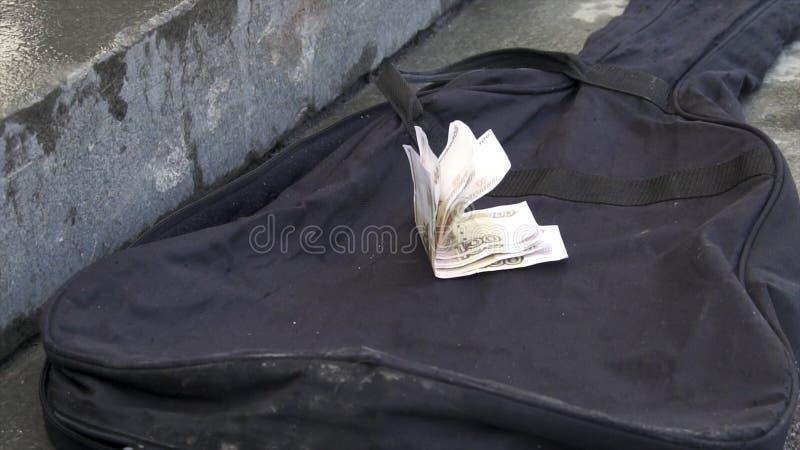Närbilden av handen ger pengar som spets och satte den på fallet av gitarren Gatamusikerpengar i olikt arkivbild
