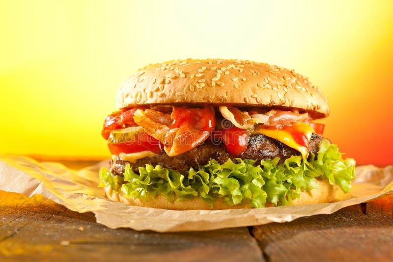 Närbilden av hem- gjorda hamburgare med brand flammar royaltyfria foton