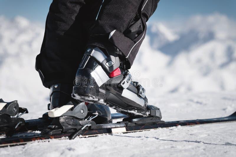 Närbilden av idrottsman nen skidåkares fot i skidar kängor som löneförhöjningar in i skidar mot bakgrunden av detkorkat arkivbild