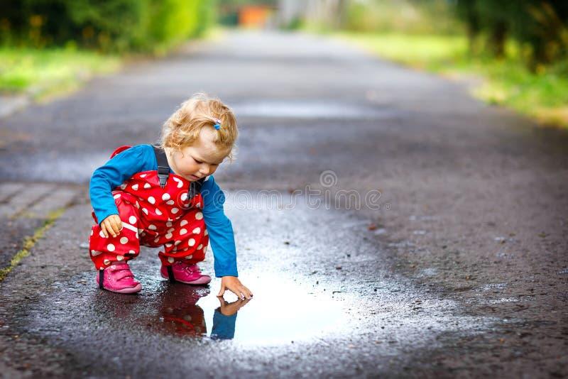 Närbilden av kängor för regn för den lilla litet barnflickan bärande och byxan och att gå under regnar snöslask, regnar på kall d royaltyfri bild