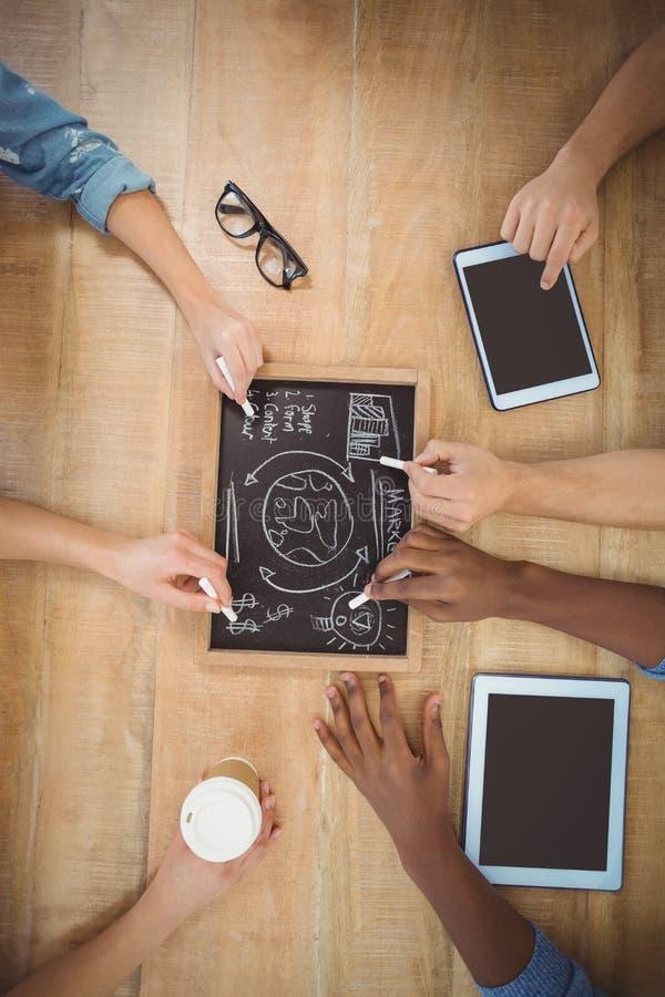 Närbilden av kantjusterade händer som skriver affärsuttryck kritiserar på, med den rörande digitala minnestavlan för personen royaltyfria bilder