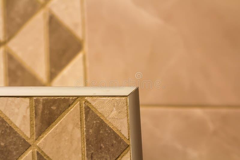 Närbilden av keramiska tegelplattor ut tränga någon med silvermetallremsan på innerväggen royaltyfri fotografi