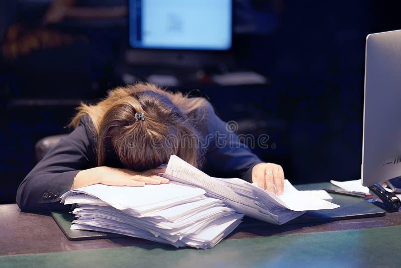 Närbilden av kontorsarbetaren bedrövas med mycket skrivbordsarbete som är främst av henne Mycket skrivbordsarbete i regeringsstäl royaltyfri bild
