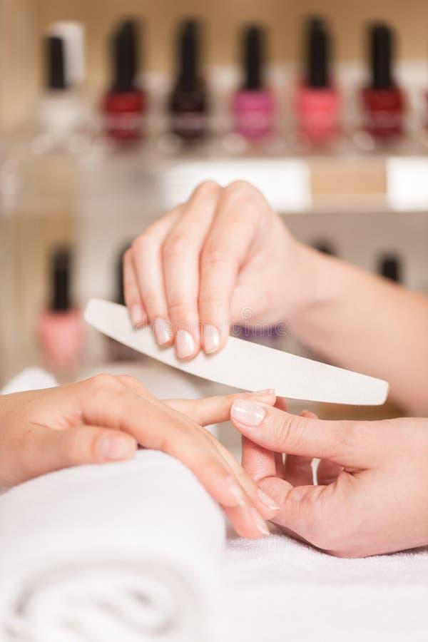 Närbilden av kosmetologhandarkiveringen spikar av kvinna i salong royaltyfri bild