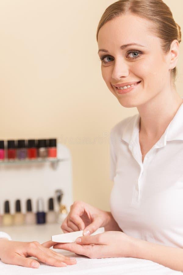 Närbilden av kosmetologhandarkiveringen spikar av kvinna i salong arkivbilder