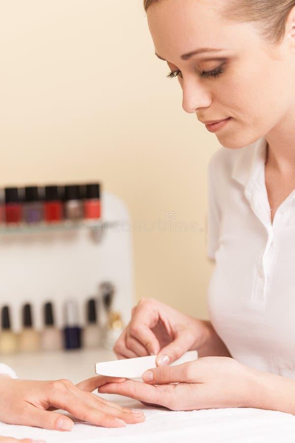 Närbilden av kosmetologhandarkiveringen spikar av kvinna i salong arkivfoton