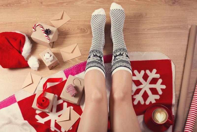 Närbilden av kvinnlign lägger benen på ryggen i varma sockor med en hjort, julgåvor, inpackningspapper, garnering och koppen av d arkivbild