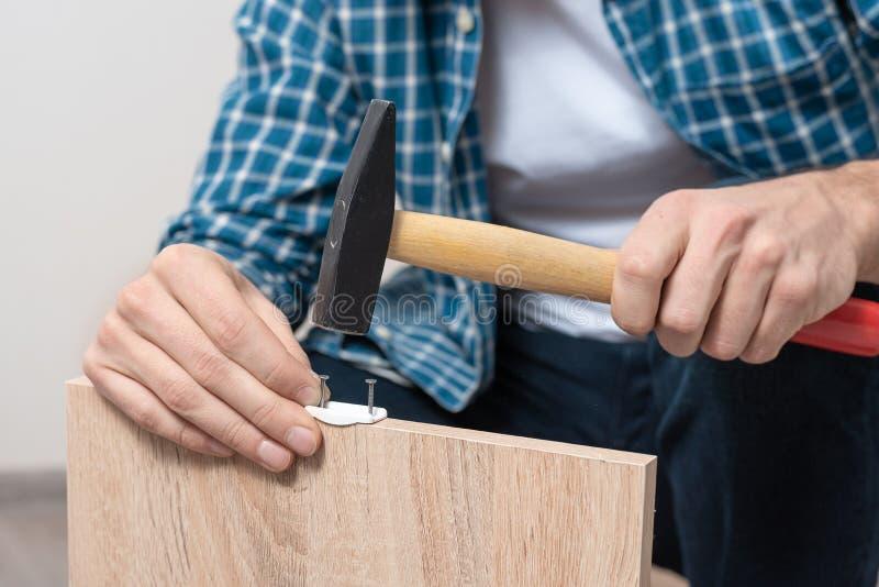 Närbilden av mäns händer med bulta för hammare spikar in i benet av tabellen arkivfoton