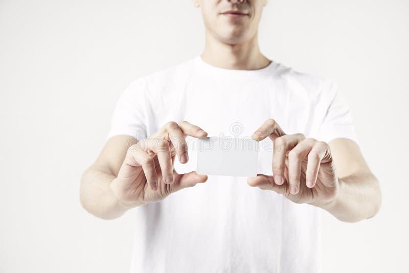 Närbilden av man` s räcker att rymma ett affärskort, bärande vit t-skjorta för grabb Vitbakgrund i studio royaltyfria bilder