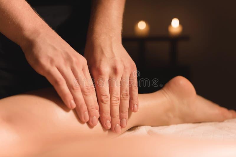 Närbilden av manhänder som gör kalvmassage av kvinnlign, lägger benen på ryggen i ett mörkt rum med stearinljus i bakgrunden Cosm royaltyfri foto