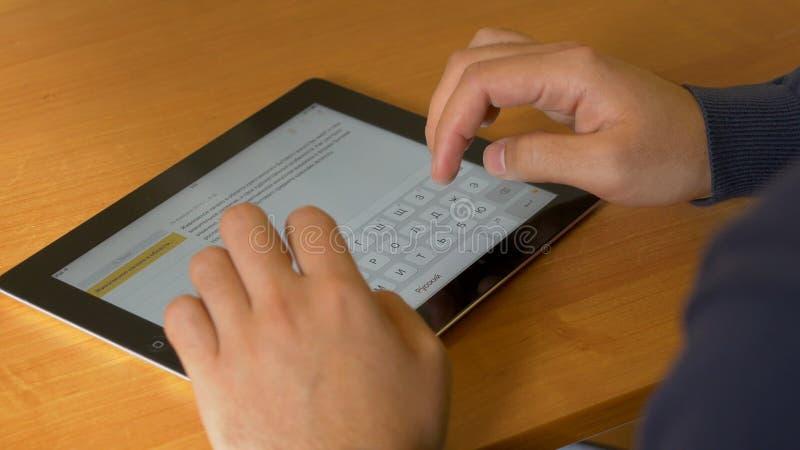 Närbilden av mannen räcker genom att använda den moderna digitala minnestavlan, och datoren på kontoret, den frontal sikten av af arkivbilder