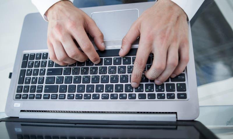 Närbilden av mannen räcker maskinskrivning på bärbara datorn fotografering för bildbyråer