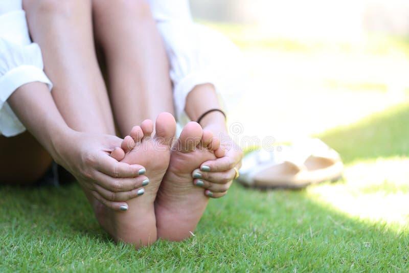 Närbilden av mening för ung kvinna smärtar i hennes fot på gräset, H royaltyfri bild