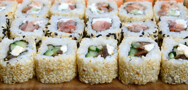 Närbilden av mycket sushirullar med olika fyllningar ligger på en träyttersida Makroskott av lagad mat klassisk japansk mat med fotografering för bildbyråer