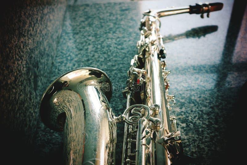 Närbilden av någon av saxofonen, jazzmusikinstrumentet, mörk signal, stenar bakgrund arkivbild