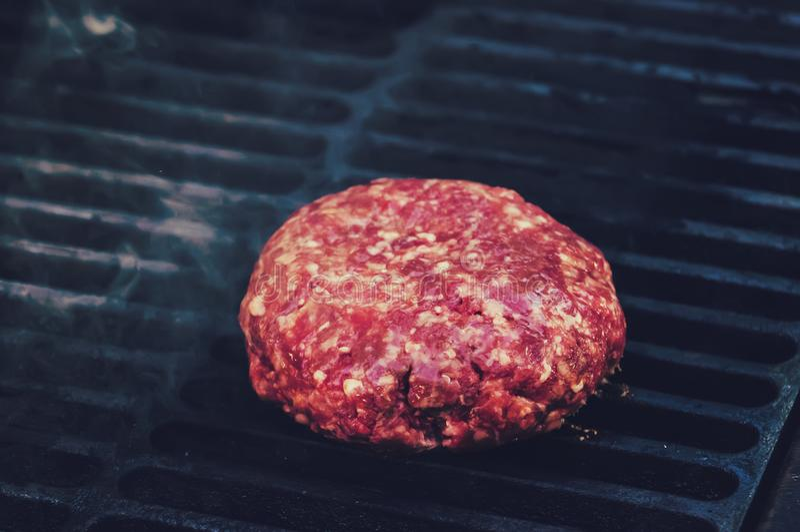 Närbilden av nötköttkotletten, för hamburgare, stekte i galler, arkivbilder