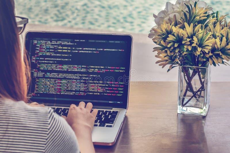 Närbilden av programmerare` s räcker arbete på källkoder över en bärbar dator på en sommardag royaltyfria foton